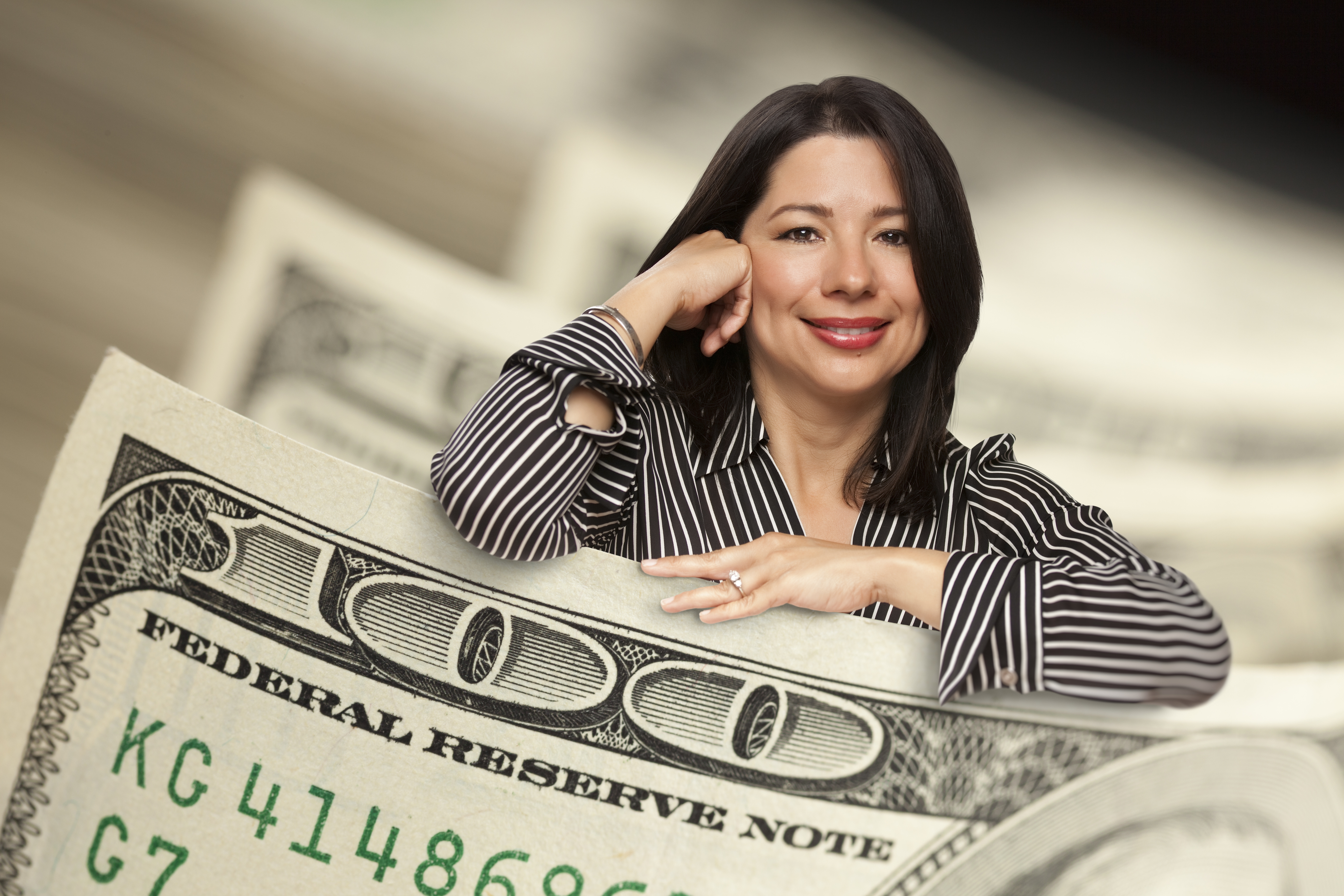 Attractive Hispanic Woman Leaning On A One Hundred Dollar Bill